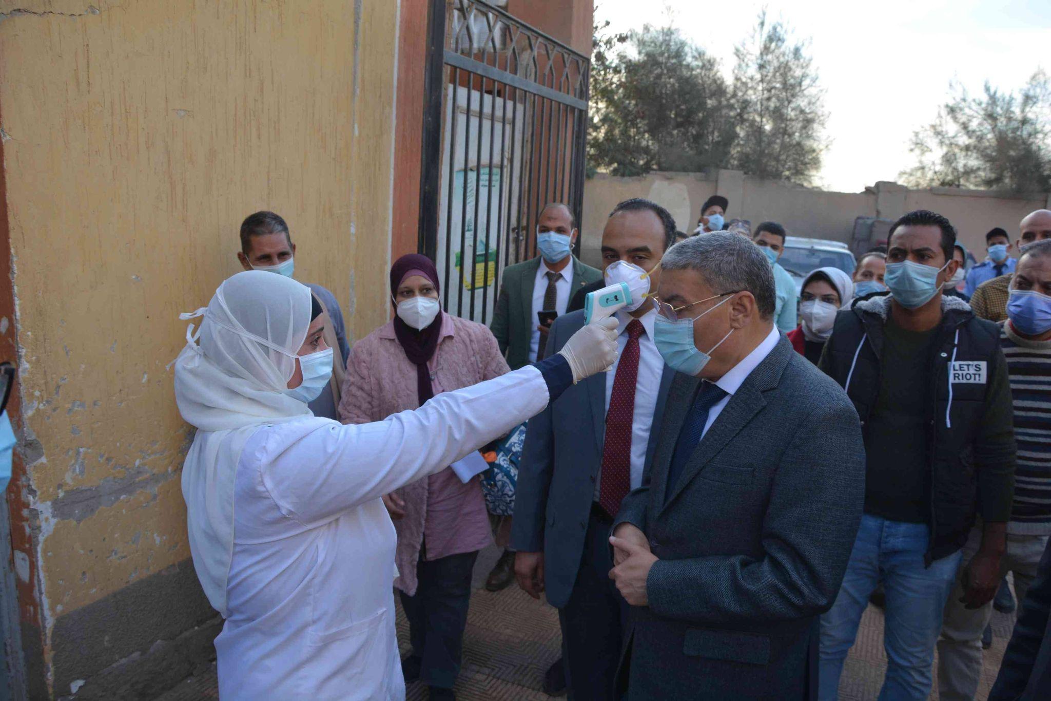 احدى الممرضات تقيس الحراة لمحافظ المنيا